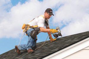 Worker repairing hail damage on shingle home in Waynesboro, Virginia - Waynesboro Roofing